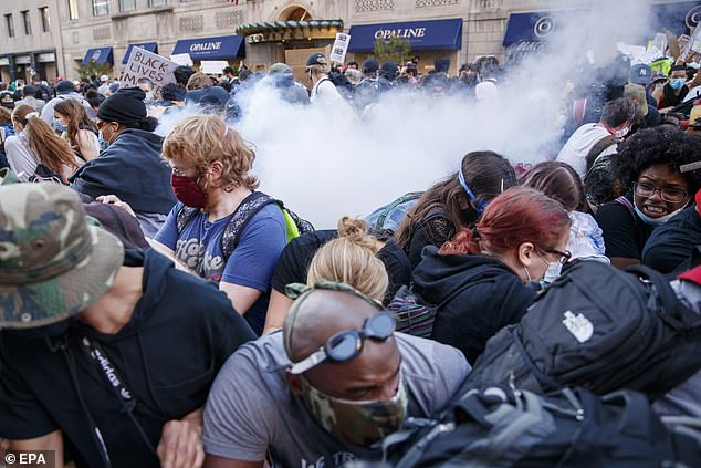 Police appear to use tear gas to disperse protesters near the White House in Washington, DC, on Sunday