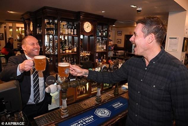 Federal treasurer Josh Frydenberg (left) cheers former AFL footballer Matthew Richardson at the Glenferrie Pub in Melbourne, Monday, June 1