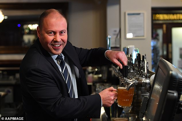 Federal treasurer Josh Frydenberg holds up a beer at the Glenferrie Pub in Melbourne to celebrate the opening of bars