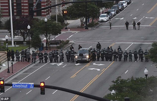 Officers with the New Hanover County Sheriff's Office and the Wilmington Police Department line up after firing tear gas while confronting protestors in downtown Wilmington