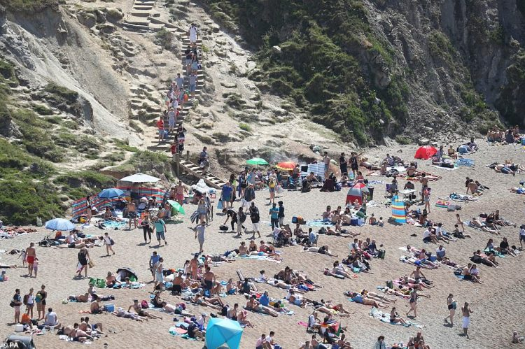 People make their way down the steps to the beach at Durdle Door, near Lulworth, today despite Dorset Council announcing that the beach was closed