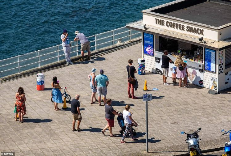 People social distance whilst waiting for their morning coffee at the Plymouth Hoe in Devon today as temperatures soar