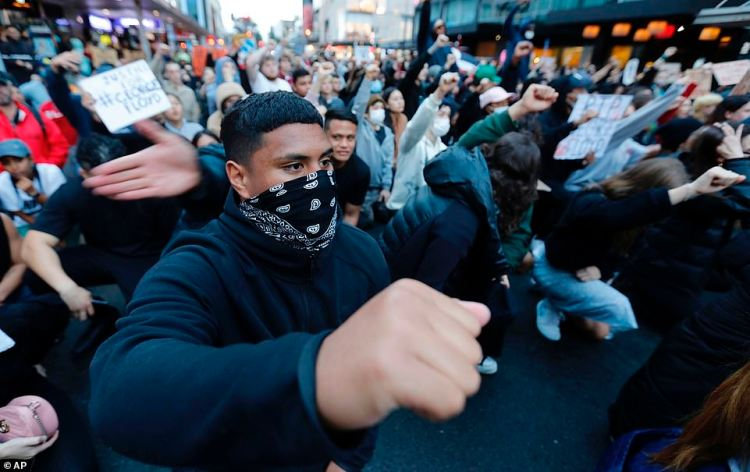 A man raises his fist while wearing a face mask at the protest. Event organisers called for protesters to practice social distancing, which became difficult as crowd numbers grew