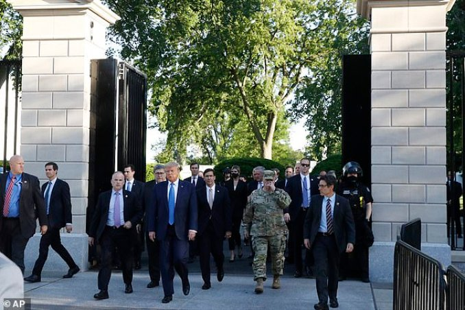 President Trump walked out of the White House surrounded by Cabinet officials, aides and security