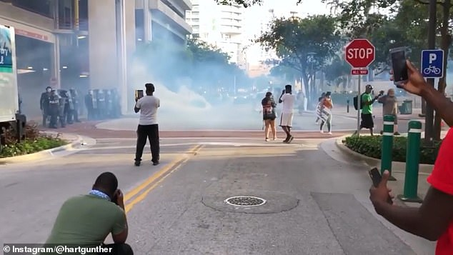 LaToya Ratlieff, 34, is seen in the orange tank top to the right holding a sign and walking away from the cops and tear gas moments before she was shot in the head with a foam rubber bullet