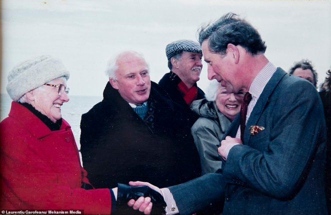 Mr Clements is pictured among crowds meeting Prince Charles in a glimpse at his life before moving to Romania