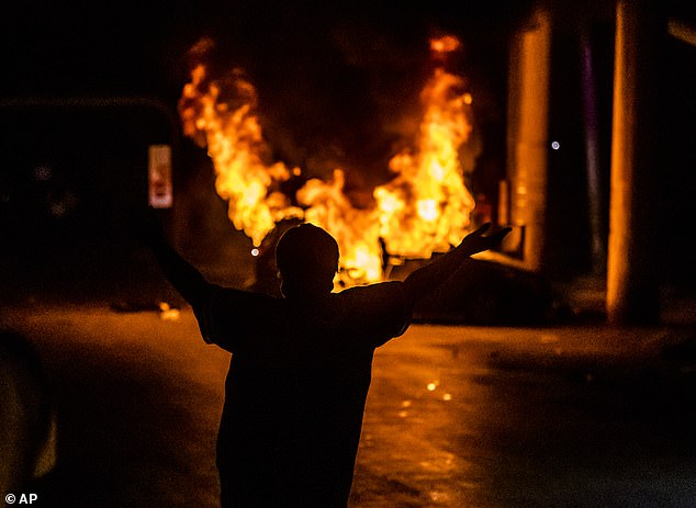 Twelve major cities have declared curfews, 17,000 troops have been activated and governors in at least 24 states called in the National Guard after demonstrations over the death of George Floyd. Pictured, a protester stands in front of a car set on fire in Texas on May 30