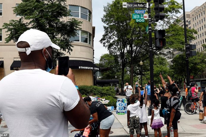 WASHINGTON, D.C.: A family has their photo taken as they point to the new sign at Black Lives Matter Plaza, which was officially renamed by the mayor of D.C.