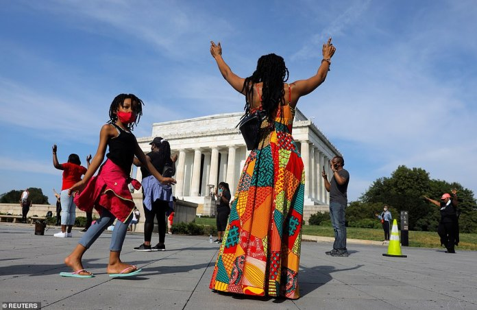 WASHINGTON, D.C .: People raise their hands near the Lincoln Memorial on Saturday morning before a demonstration expected to be the largest to date against racial inequality in the aftermath of the death of George Floyd in police custody in Minneapolis