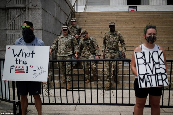 WASHINGTON, D.C .: Protesters holding placards while the National Guard prepares for Washington D.C.