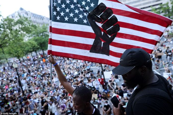Pilomena Wankenge of DC Freedom Fighters waves an American flag to a crowd gathered at the John A. Wilson Building