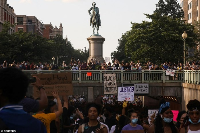 Protesters heading to the White House are seen in front of the statue of Lt. Gen. Scott Winfield Scott