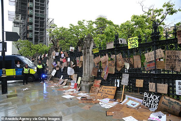 Fences outside Parliament have been decorated with signs calling for action