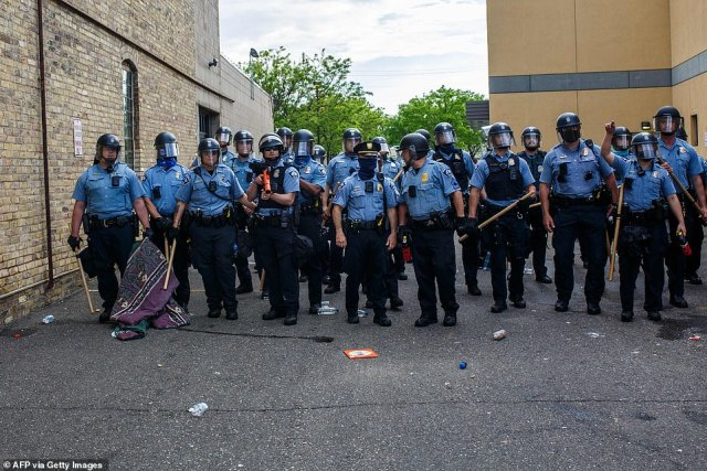 Minneapolis Police officers stand in a line while facing protesters demonstrating against the death of George Floyd outside the 3rd Precinct Police Precinct in Minneapolis - photo from May 27