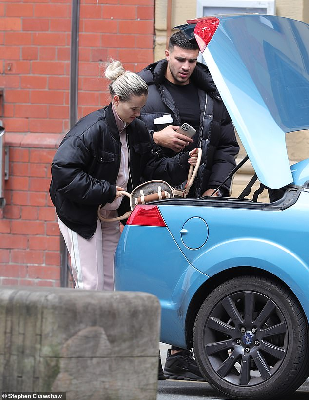 On the road: boxer Tommy wrapped in a quilted jacket and hanging on his phone while the Hertfordshire native removes objects from the trunk of the vehicle