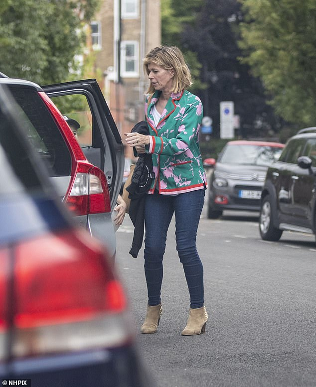Helping hand: Kate helped her son Billy in their parked car and wore his black sweater in her hand
