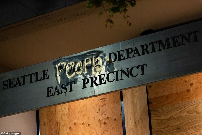 A degraded sign outside the Seattle East Precinct Police Service is seen Tuesday in Seattle, Washington. The station was abandoned on Monday and is now under the control of CHAZ authorities