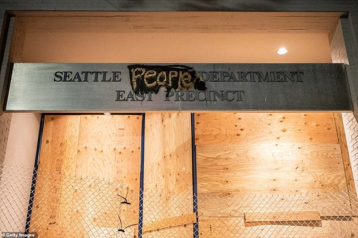A disfigured sign outside the eastern Seattle Police Department after protesters chased the cops and set up a six-block `` free zone '' in memory of George Floyd
