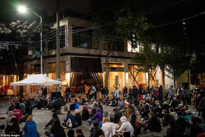 On Tuesday, people are sitting on the street in front of the East Precinct. The area had been the site of tensions and laconic confrontations between the police and the demonstrators before the police went into the compound and withdrew from the area