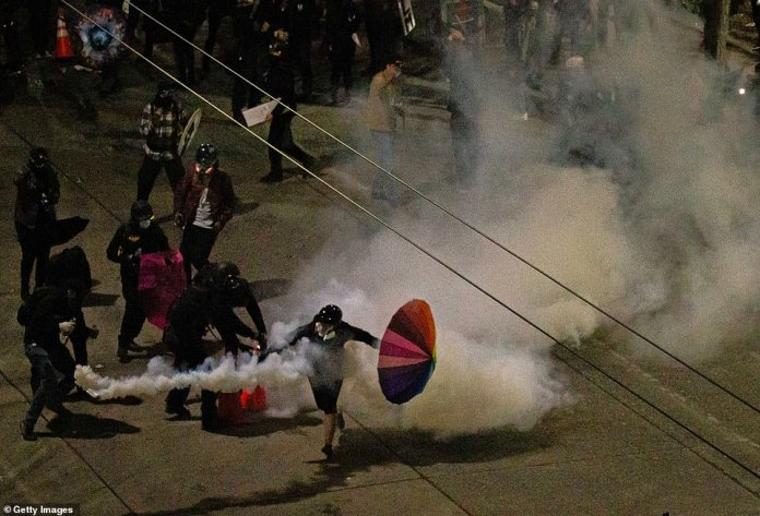 Protesters clash with law enforcement near the east precinct of the Seattle Police Department shortly after midnight