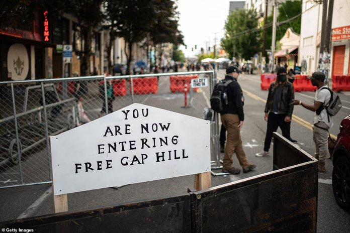 A sign is seen on a barrier at the entrance of the so-called