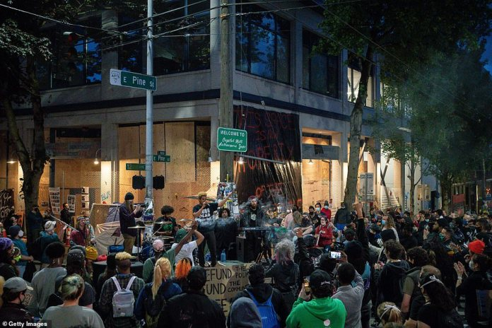 A group performs a free performance in front of the Seattle East Precinct Police Department in the so-called