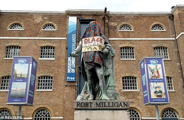 A debate has been raging across Britain over the suitability of various statues, such as the above, showing a monument to slave owner Robert Milligan covered with a blanket and a placard reading 'Black Lives Matter' near Canary Wharf before it was removed by workers
