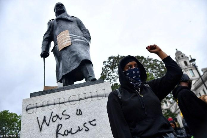 Ein Demonstrant reagiert vor Graffiti auf eine Statue von Winston Churchill auf dem Parliament Square während eines Protestes gegen Black Lives Matter in London am 7. Juni nach dem Tod von George Floyd, der in Polizeigewahrsam in Minneapolis starb