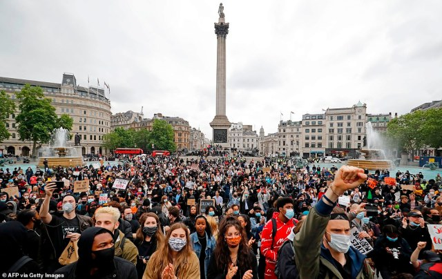 Activists, some wearing face coverings or face masks as a precautionary measure against COVID-19, hold placards as they attend a Black Lives Matter protest at Nelson's Column in Trafalgar Square yesterday