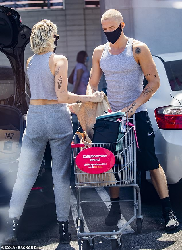 Full cart: Miley was joined by boyfriend Cody Simpson, 23, as they filled their cart to the brim with bags of essential goods