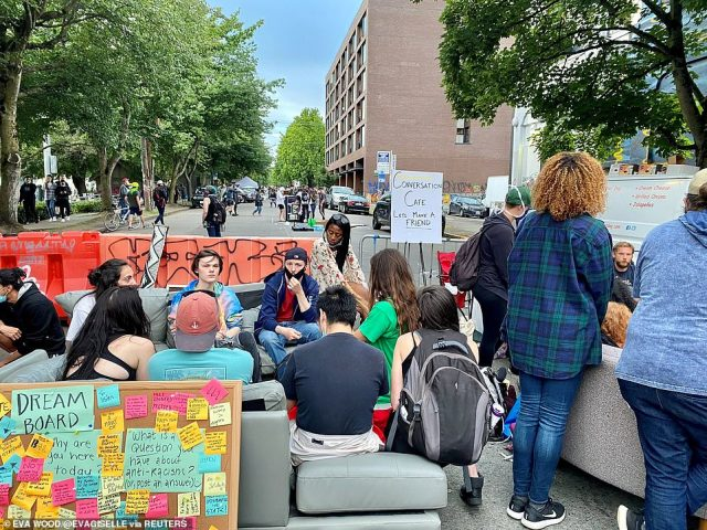 "People sit near a barricade next to a sign reading ""Conversation Cafe"" in the Seattle CHAZ"