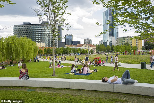 People sit in the grass and walk the paths at Biblioteca degli Alberi Park in De Porta Nuova Park, Milan, today