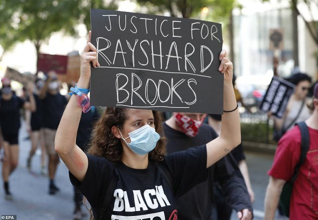 A woman holds up a sign which reads 'Justice for Rayshard Brooks' during a demonstration in Atlanta on Saturday