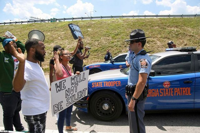 Demonstrators hold signs and make gestures toward a George state trooper near the Wendy's fast food restaurant on University Avenue in Atlanta on Saturday
