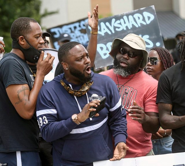 Protesters with cell phones gathered near the Wendy's fast food restaurant on University Avenue in Atlanta on Saturday