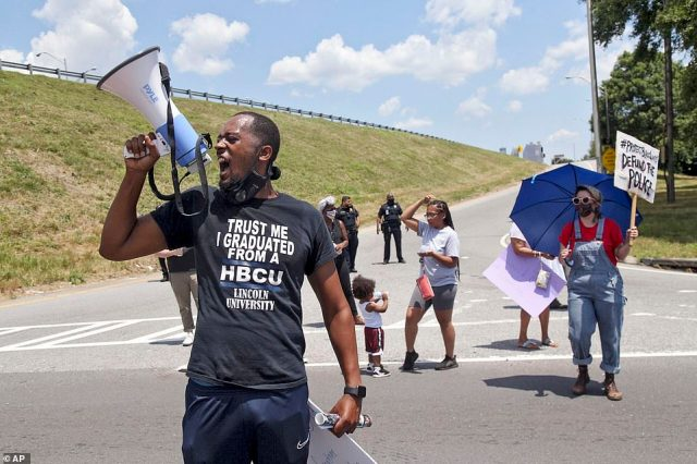 One protester holds a megaphone while chanting slogans near the Wendy's fast food restaurant on University Avenue in Atlanta on Saturday
