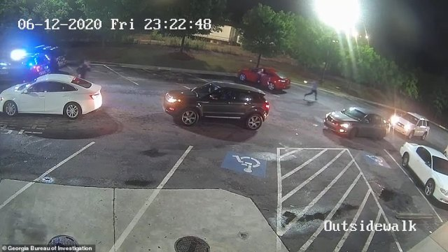 Brooks (far right) appears to turn and point the stolen taser, as one officer takes cover by the red car and the second officer pursues from the far left of the image
