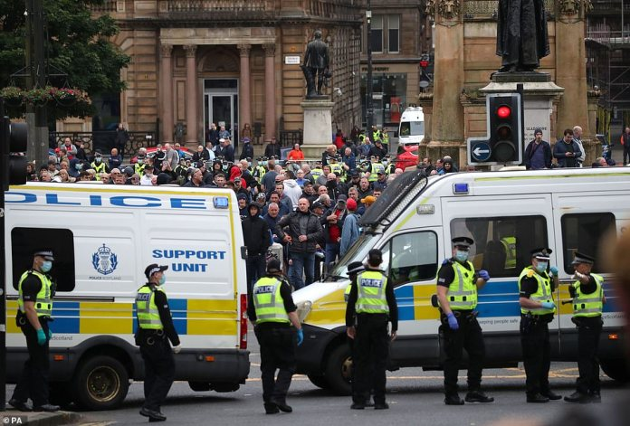 Police and members of the Loyalist Defense League in George Square in Glasgow during a demonstration between people calling for the removal of a statue of Metropolitan Police founder Robert Peel and counter-demonstrators