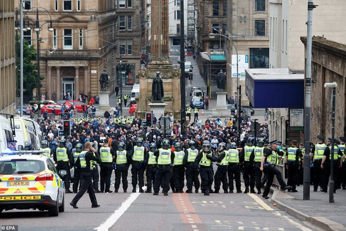 Police present as a large group of people stand in George Square in Glasgow