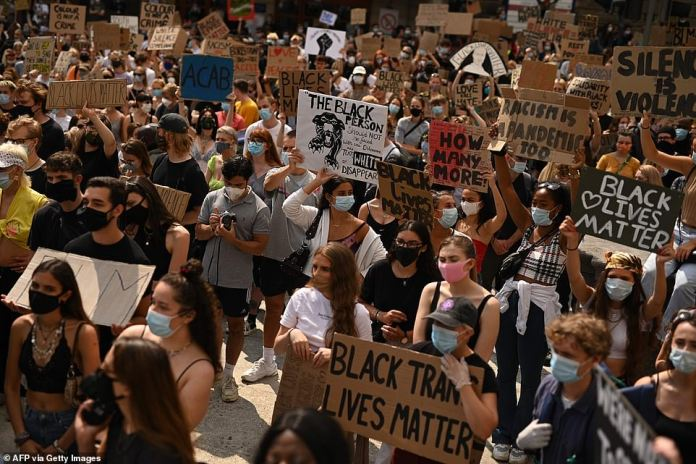 Protesters hold up signs at a rally in support of the Black Lives Matter and Black Voices Matter movements in central Leeds