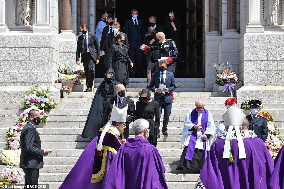 Les personnes en deuil portant des masques noirs quittent la cathédrale après la cérémonie.  Le Prince Albert et son épouse la princesse Charlene conduisent la famille royale sur les marches de l'édifice