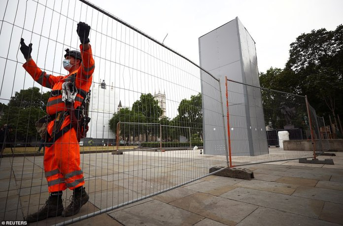 Worker wearing protective gear begins to remove metal box around former Prime Minister