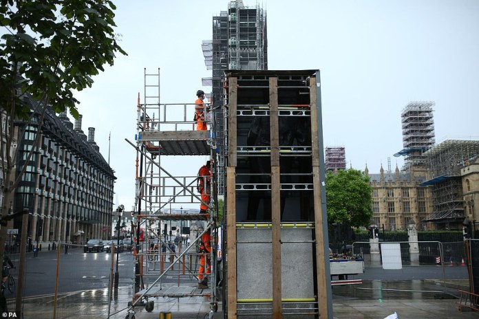 A team of workers dismantles the protective box around the statue of the former Prime Minister