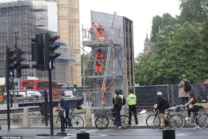 Police officers and construction workers arrive at Parliament Square in London as work begins on removing the protective panel