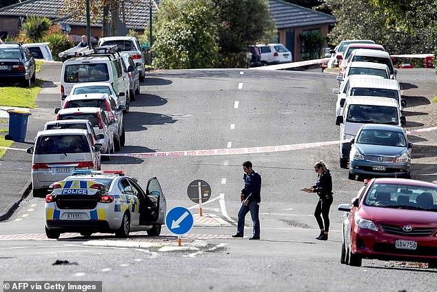 Des enquêteurs examinent la scène de l'incident dans l'ouest d'Auckland (photo) vendredi matin, après que trois personnes - dont deux policiers - ont été transportées à l'hôpital
