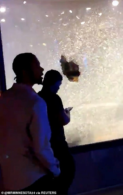 People pass by shattered glass on a shopfront after a shooting in Minneapolis