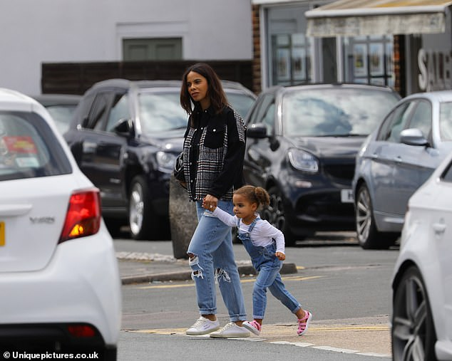 Adorable: The Saturday's star held hands with her youngest daughter who was dressed in a denim dungarees and plain white T-shirt