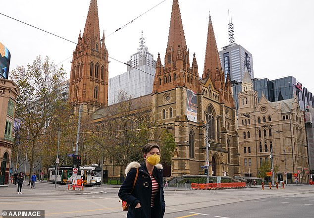 A woman in a face mask is seen walking past St Paul's Cathedral in Melbourne on June 21 (pictured) as coronavirus cases rise across the city