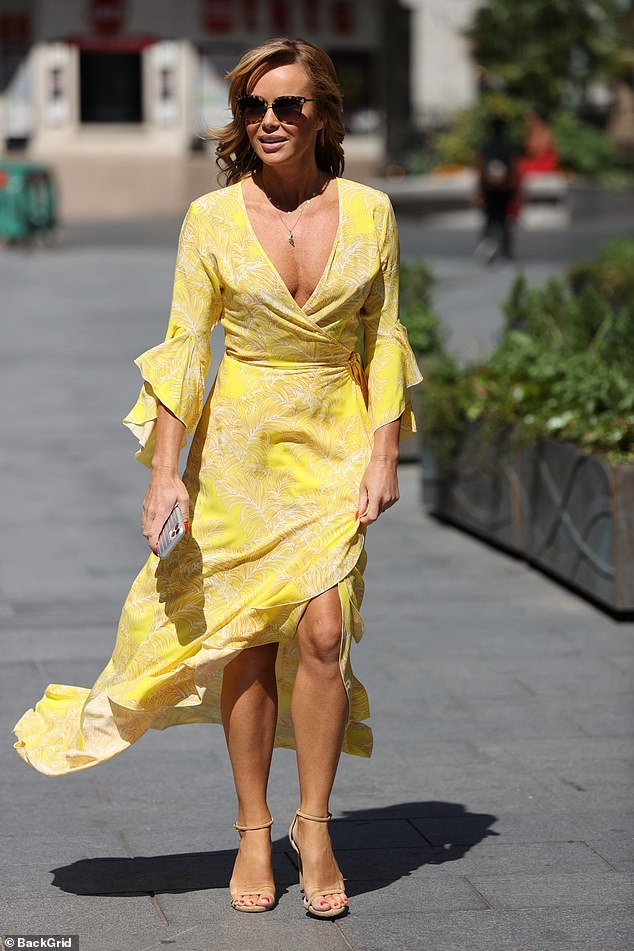 Mellow yellow: Amanda Holden has held on his low-cut wrap dress as she avoided a wardrobe malfunction while leaving the Heart FM radio studios in London on Monday