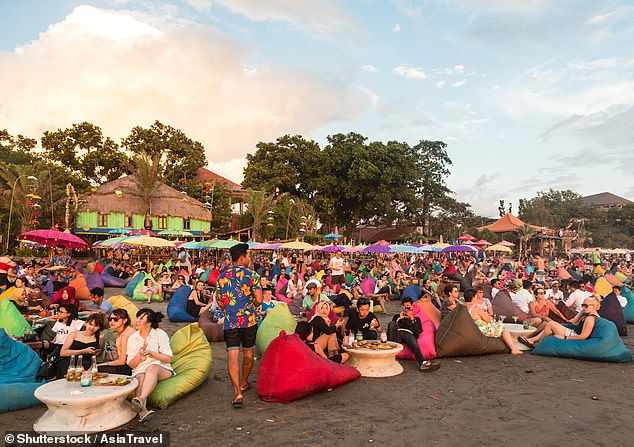 Australian surfers, yogis and party goers typically flood the holiday island this time of year seeking a winter escape (pictured: Travellers on Kuta Beach in Seminyak)